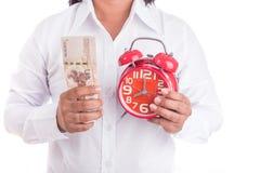 Kobieta trzyma Tajlandzkiego pieniądze i czerwień budzika odizolowywającymi na bielu obraz royalty free