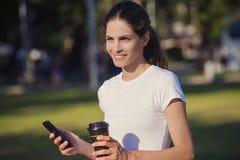 Kobieta trzyma telefon i napój przy parkiem Obrazy Stock