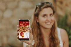 Kobieta trzyma telefon komórkowego z online pizzy dostawy sklepem i pokazuje zdjęcie stock