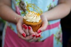 Kobieta trzyma toffee babeczkę w Kwiecistej sukni z malującymi gwoździami Obrazy Royalty Free
