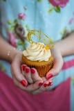 Kobieta trzyma toffee babeczkę w Kwiecistej sukni z malującymi gwoździami Obraz Royalty Free