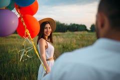 Kobieta trzyma wiązkę balony, para w polu zdjęcia royalty free