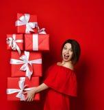 Kobieta trzyma wiele pudełka w czerwieni sukni obrazy stock