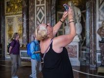 Kobieta turyści chapią smartphone fotografię Versailles pałac ceili Fotografia Royalty Free