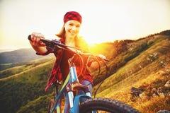 Kobieta turysta na bicyklu na szczyciefal tg0 0n w tym stadium góry przy zmierzchem outdoors Obrazy Stock