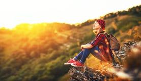 Kobieta turysta na szczyciefal tg0 0n w tym stadium góry przy zmierzchem outdoors podczas podwyżki Zdjęcia Stock