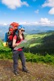 Kobieta turysta w górach czyta mapę Obrazy Royalty Free