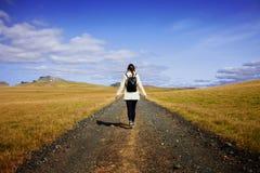Kobieta turysta z plecakiem na tło drodze W kierunku celu obraz stock