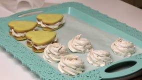 Kobieta tworzy pianki z workiem cukierniczym W pobliżu na tacy są kanapki z piankami zdjęcie wideo