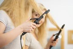 Kobieta używa włosianego curler fotografia stock