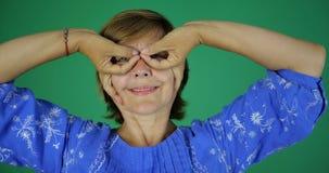 Kobieta uśmiecha się gest palce i robi w postaci szkieł na jej twarzy zbiory wideo