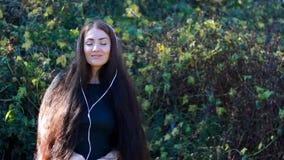 Kobieta uśmiecha się piosenkę z ona i cieszy się w hełmofonach oczy zamykał plenerowego zbiory