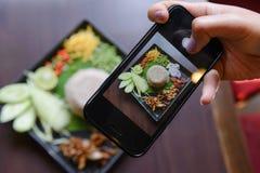 Kobieta użytkownika mądrze telefon brać obrazek Rice mieszał z krewetkowym pasty Kao Cluk Ka Pi Obraz Stock