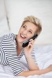 Kobieta Używa Cordless telefon Up W łóżku Podczas gdy Przyglądający Zdjęcie Royalty Free