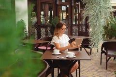 Kobieta używa cyfrową pastylkę i pijący kawę obraz stock