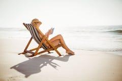 Kobieta używa cyfrową pastylkę na plaży Obraz Stock
