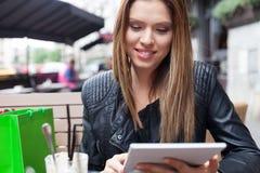 Kobieta używa cyfrową pastylkę relaksować obsiadanie w krześle w kawiarni obrazy royalty free