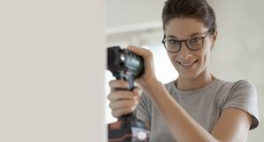 Kobieta używa działanie i świder w jej nowym domu obraz stock