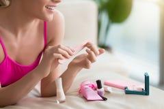 Kobieta używa gwóźdź odbojnicę gdy robić manicure'owi obrazy stock