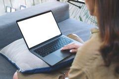 Kobieta używa i dotykajÄ…cy na laptopu touchpad z pustym bielu ekranem w żywym pokoju podczas gdy siedzÄ…cy zdjęcia stock