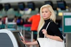 Kobieta używa jaźń - odprawa kiosk Zdjęcia Stock