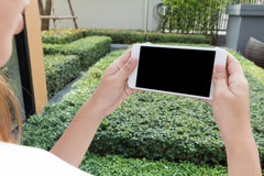 Kobieta używa jej mobilnego mądrze telefon outdoors parkuje Fotografia Stock
