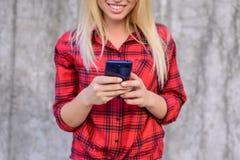 Kobieta używa jej smartphone dla surfować internet, ogląda śmiesznych wideo na internecie Młoda dziewczyna z promieniejącym uśmie obrazy royalty free