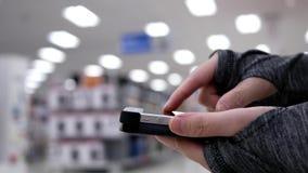 Kobieta używa jej telefon komórkowego na pięknym zamazanym oświetleniowym tle zdjęcie wideo