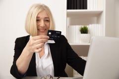 Kobieta u?ywa kart? kredytow? online w biurze fotografia royalty free