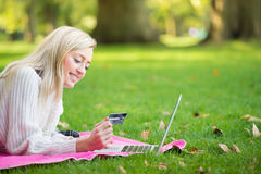 Kobieta używa kredytową kartę robi zakupy online z laptopem w normie Zdjęcia Royalty Free