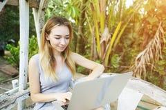 Kobieta używa laptop dla pracy na słonecznym dniu, tło światło słoneczne zieleni palmy w Tajlandia, Phuket zdjęcia stock
