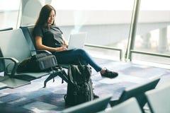 Kobieta u?ywa laptop w lotnisku podczas gdy siedz?cy zdjęcia royalty free