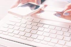 Kobieta używa mądrze telefon i laptop trzyma kredytową kartę Obrazy Royalty Free