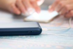 Kobieta używa mądrze telefon podczas gdy ładować na władza banku obraz stock