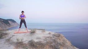 Kobieta używa mądrze zegarek przed trenować w naturze, po czym zaczyna trening zbiory wideo