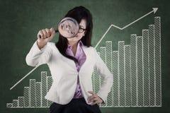 Kobieta używa magnifier monitorować biznesowego przyrosta obraz royalty free