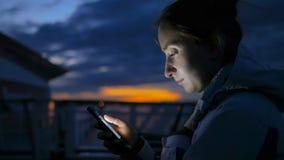 Kobieta używa pionowo smartphone na pokładzie statek wycieczkowy przy nocą zdjęcia royalty free
