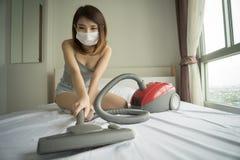 Kobieta używa próżniowego cleaner przy homeBeau podczas gdy czyścić białego łóżko obraz royalty free