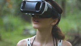 Kobieta używa rzeczywistości wirtualnej szkła w dżungli w zwolnionym tempie, orbita strzał zbiory wideo