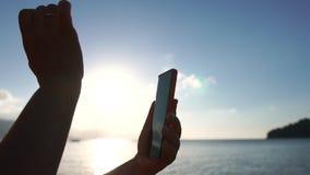 Kobieta używa smartfona przeciwko morzu w zwolnionym tempie przy wschodzie słońca zbiory wideo
