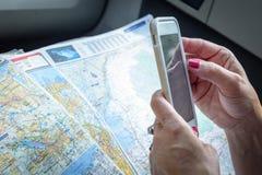 Kobieta używa smartphone i mapę planować wycieczkę Zdjęcie Stock