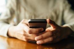 Kobieta u?ywa smartphone na drewnianym stole w kawiarni obrazy stock