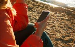 Kobieta używa smartphone obsiadanie na plaży przy zmierzchem fotografia stock