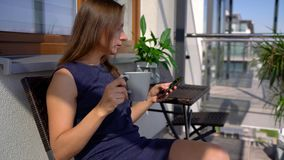 Kobieta używa smartphone podczas gdy podczas gdy pijący ranek kawę na balkonie zbiory wideo