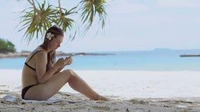 Kobieta używa smartphone przy plażowy pić Zamyka up kobiety mienie zdjęcie wideo