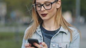 Kobieta używa smartphone w Europejskim mieście Modniś dziewczyna wyszukuje internet na telefonie, texting i komunikować, zbiory