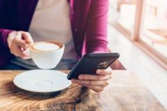 Kobieta używa smartphone w sklep z kawą Zdjęcia Royalty Free