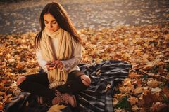 Kobieta używa smartphone w spadku Jesieni dziewczyna ma mądrze rozmowę telefoniczną w słońce racy ulistnieniu Portret Kaukaski Zdjęcie Royalty Free