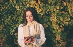 Kobieta używa smartphone w spadku Jesieni dziewczyna ma mądrze rozmowę telefoniczną w słońce racy ulistnieniu Portret Kaukaski Obraz Stock