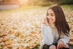 Kobieta używa smartphone w spadku Jesieni dziewczyna ma mądrze rozmowę telefoniczną w słońce racy ulistnieniu Portret Kaukaski Zdjęcia Royalty Free